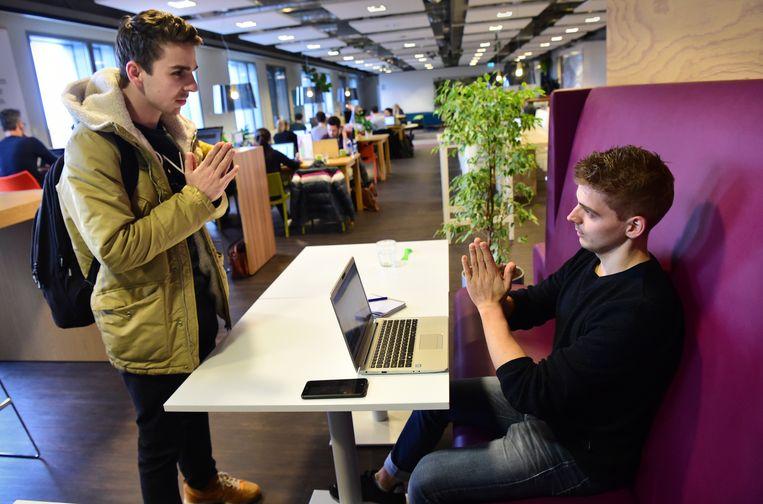 Twee jonge ondernemers in Den Bosch geven gehoor aan het advies van hogerhand om fysiek contact te vermijden door elkaar op een alternatieve manier te begroeten. Beeld Marcel van den Bergh / de Volkskrant