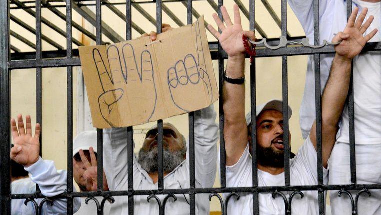 Steunbetuigingen aan de Moslim Broeders buiten de rechtbank in Egypte waar 155 Moslim Broeders een gevangenisstraf opgelegd kregen. Op het bord is het 'rabaa'-symbool te zien, het wordt gebruikt door tegenstanders van de recente coup door legerleider Al-Sisi Beeld ap