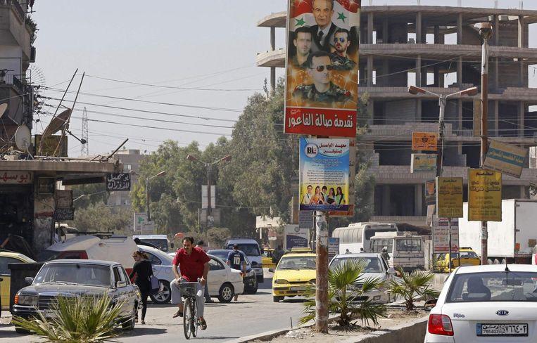 Een poster in de hoofdstad Damascus, met onder president Bashar al-Assad. Beeld AFP