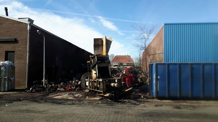 Een verbrande balenpers en afvalresten van tapijtproductie.