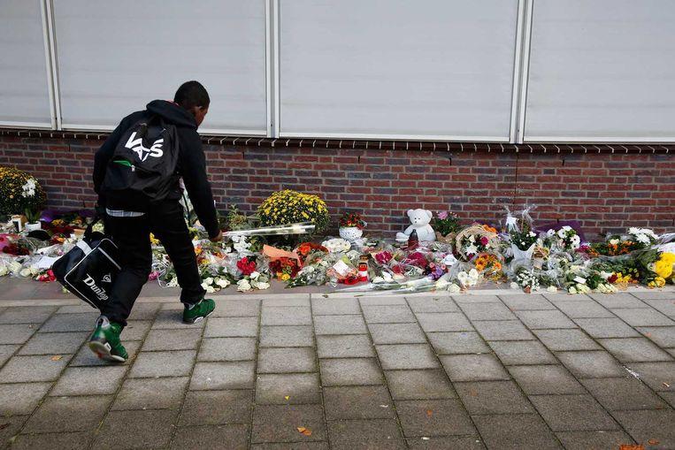 Een jongen legt bloemen ter ere van de 15-jarige Wesley. De leerling van het Corbulo College werd op het schoolplein doodgestoken door een 16-jarige medeleerling. Beeld anp