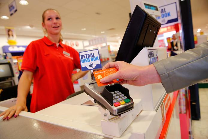 Een contactloze pinbetaling in een Kruidvat winkel. Doordat de pincode bij veel betalingen niet meer nodig is, lijken meer kinderen die te vergeten.