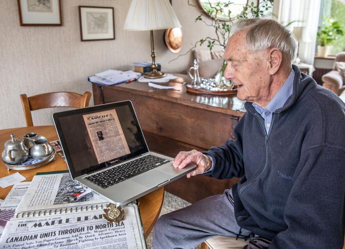 Ton Nauta met de digitale kopie van de Maple Leaf, die hij van de Canadese soldaat Fred Arsenault kreeg. Naast de laptop de badge van Arsenault's regiment Cape Breton Highlanders.
