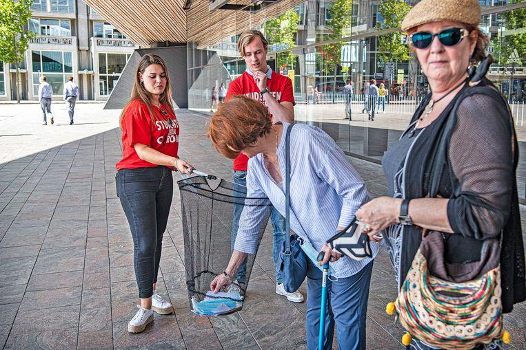 Studenten delen in Rotterdam flyers en mondkapjes uit om het bewustzijn over Covid-19 te vergroten. Beeld Guus Dubbelman / De Volkskrant