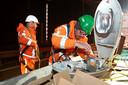 Een monteur treft de voorbereidingen die nodig zijn om dit nieuwe armatuur aan de Merwedebrug te kunnen ophangen.