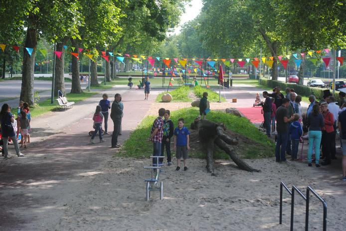 De rode sintelbaan omgeeft het speelterrein met zand, schommel, klimbomen en een omheind sportveld.