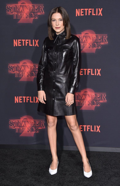 De actrice draagt hier een lederen jurk van Calvin Klein.