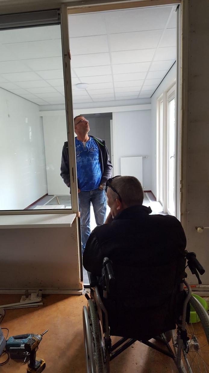 Ed Warnar (op de rug gezien) bekijkt de nieuwe zorgunit die zojuist in zijn achtertuin is geplaatst.