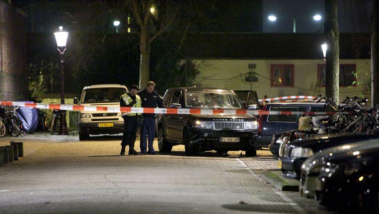 De politie heeft op 29 december 2012 in de Amsterdamse Staatsliedenbuurt de plek afgezet waar een auto met kalasjnikovs onder vuur is genomen. Beeld null