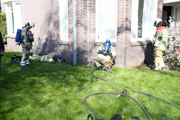De brandweer probeert ruimte te vonden om onder het huis te blussen.