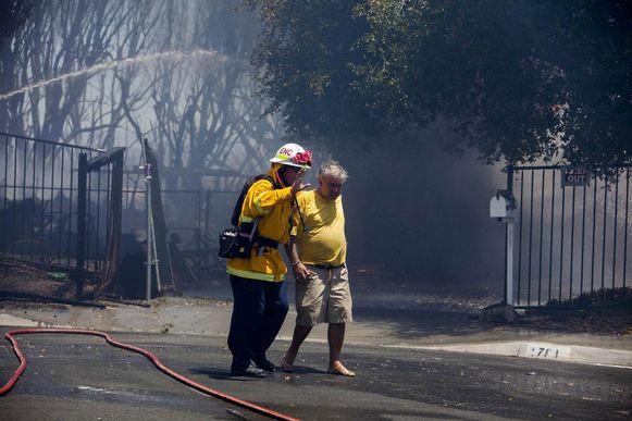 Een brandweerman leidt een man weg bij het brandende huis van zijn moeder in Carlsbad