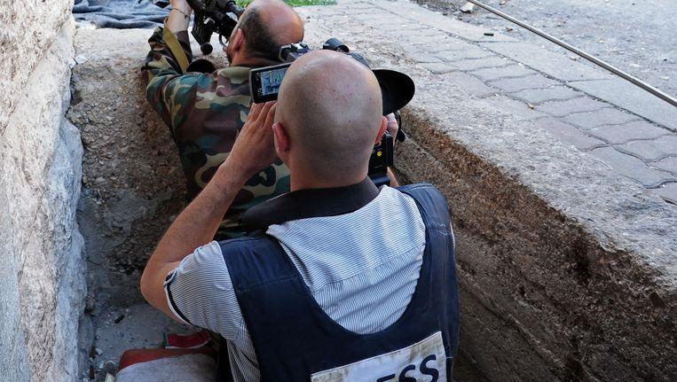 Een journalist filmt een Syrische soldaat tijdens gevechten met het Vrije Syrische Leger in Maaloula in september. Sommige van de rebelleneenheden worden gelinkt aan de terreurbeweging al-Qaida. Beeld AP