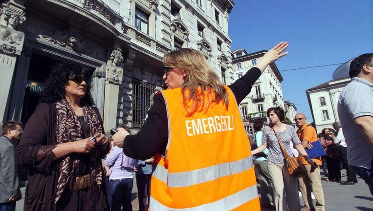 Een vrijwilliger helpt tijdens het evacueren van mensen in Milaan. Beeld epa
