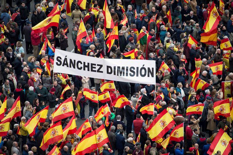 """Demonstranten houden een doek met opschrift """"Neem ontslag, Sánchez"""" op het Plaza de Colón vast. De betoging werd georganiseerd door de rechtspopulistische partij Vox om tegen de socialistische minderheidsregering van Pedro Sánchez en voor nieuwe verkiezingen te demonstreren."""
