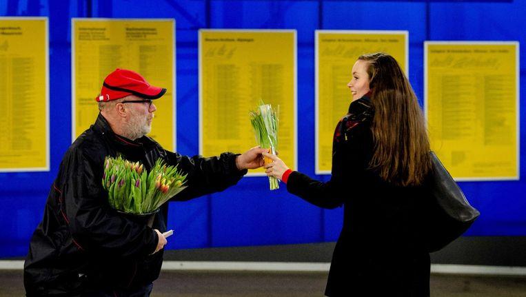 Een NS-medewerker deelt tulpen uit tijdens 'Random Acts of Kindness week' begin maart. Beeld epa
