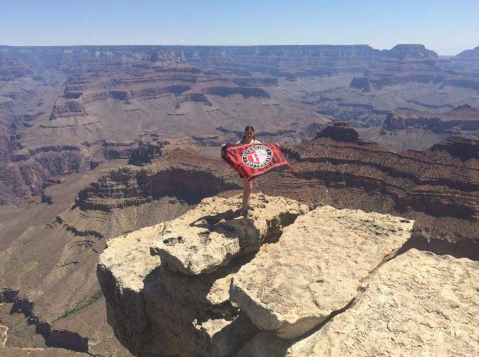 Faith IJzerman staat op duizelingwekkende hoogte, maar pakt in de Grand Canyon toch nog even de Feyenoordvlag erbij.