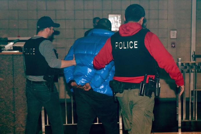 Geboeid wordt de zanger na zijn arrestatie afgevoerd.