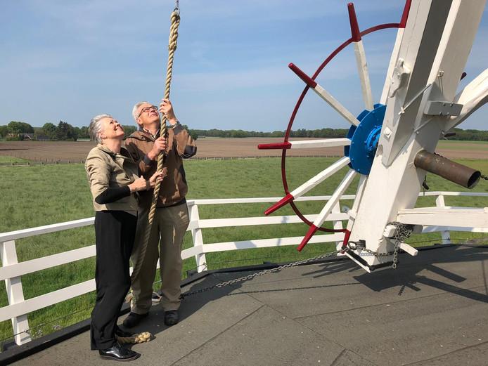 Bijschrift foto: Wethouder Marijke van Haaren zet met molenaar Bennie Mensink de molen in werking. Nationale Molendag in Neede is met deze handeling geopend.