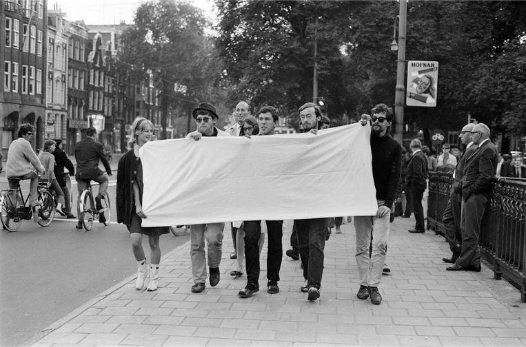 Provo's protesteren met een wit spandoek. Beeld anp