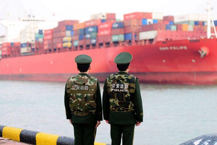 Chinese politiemannen zien een containerschip wegvaren.