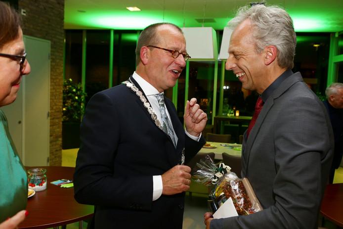 Theo Segers is hier net geïnstalleerd als nieuwe burgemeester van Molenlanden. Burgemeester Sjors Fröhlich (rechts) van Vijfheerenlanden feliciteert zijn collega.