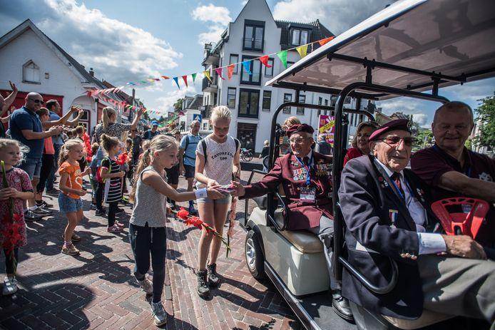 Frank Ashleigh voor in een golfkarretje tijdens een vrolijke rondrit in Oosterbeek ter gelegenheid van de Airborne Wandeltocht  op 1 september.