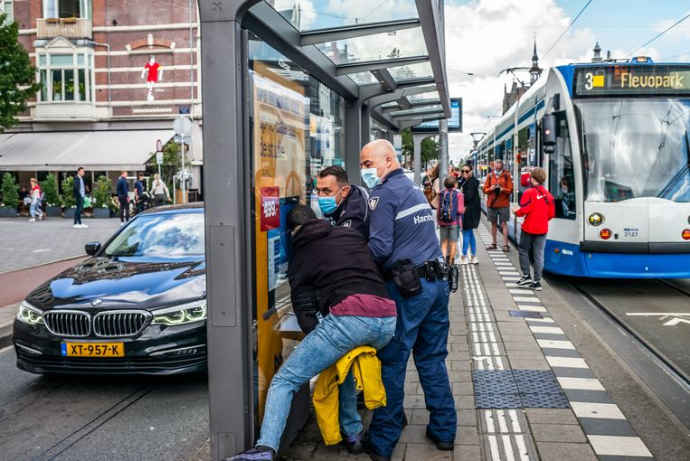Een man wordt opgepakt door handhavers van de GVB.  Beeld Joris Van Gennip
