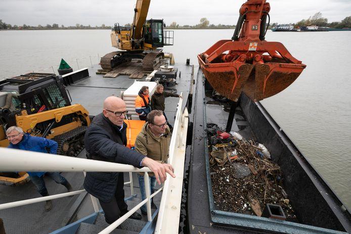 Johan van den Hout luistert naar wat Ruud van Groesen directeur van K3 te vertellen heeft over de aanpak van zwerfafval in de Koornwaard. Met de graafmachine word het zand in de stortkoker (achter de graafmachine) gegooid het zwerfafval drijft naar boven en word vervolgens weer met de graafmachine in de afvalbakboot gegooid.