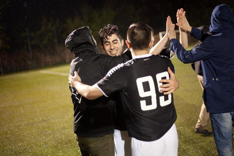 De Palestijnse speler Elias Shehadee wordt geknuffeld door zijn teamgenoten. Beeld Piotr Malecki
