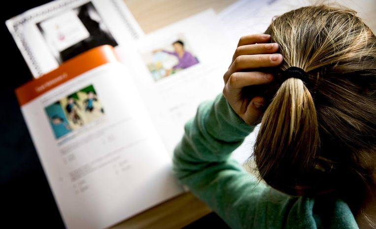 Een leerling van groep 8 buigt zich over een eindtoets. Beeld ANP