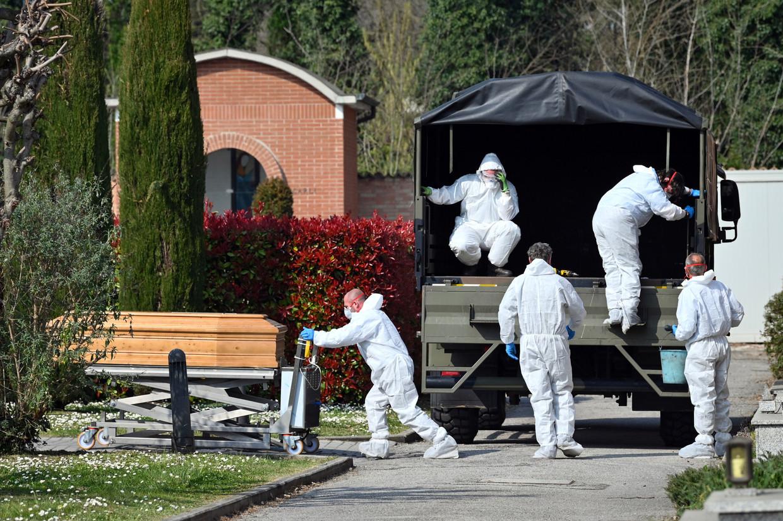 Een konvooi van Italiaanse legerwagens gevuld met dode lichamen wordt uitgeladen bij aankomst in Bergamo.  Beeld null