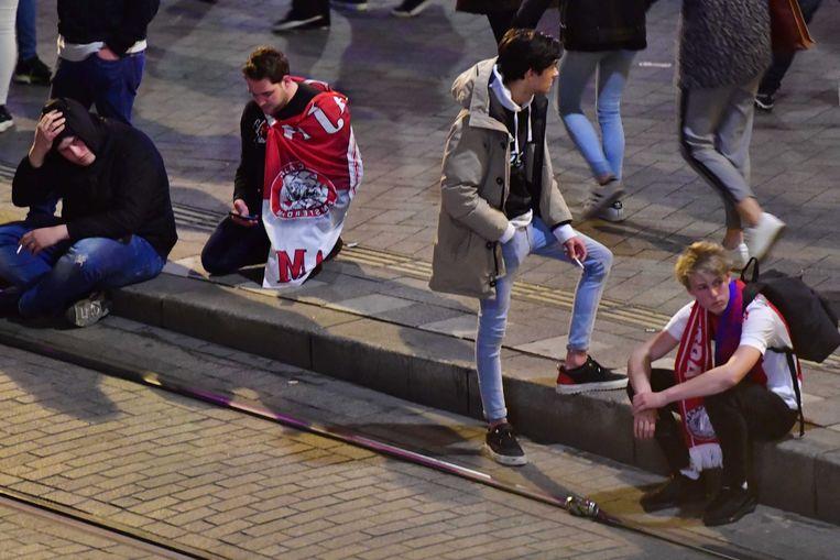 Supporters op het Leidseplein verwerken hun verdriet na de verloren wedstrijd van Ajax tegen Tottenham Hotspur Beeld ANP