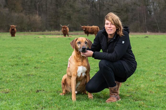 Christel Weusthof met hond Zito in het weiland waar de Schotse hooglanders grazen. Vanaf komend najaar kijken dementerende mensen in de nieuwe dagbesteding daar op uit.