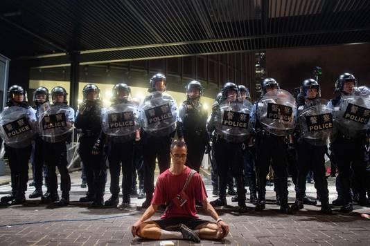 Een demonstrant zit voor een rij oproerpolitie. Er werden 100 mensen opgepakt vanwege ongeregeldheden.
