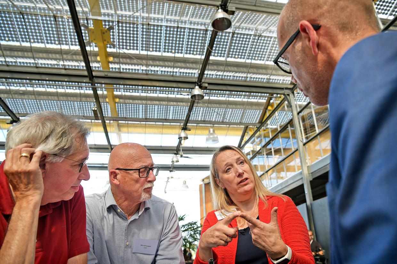 Mirella Visser praat dinsdag met Jaco Stremler, directeur luchtvaart bij het ministerie van Infrastructuur en Milieu, tijdens de inloopbijeenkomst in Vijfhuizen. Beeld Guus Dubbelman/de Volkskrant