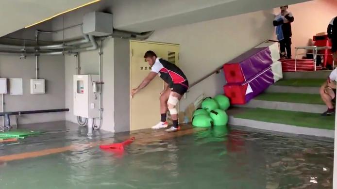 Een speler van het nationale rugbyteam van Japan probeert droge voeten te houden in het onder water gelopen  Chichibunomiya Rugby Stadion in Tokio.