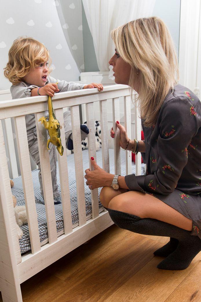 Moeder en slaapcoach Susanne Willekes bij het ledikantje met haar jongste zoon