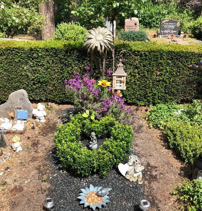 Het grafje in Haaksbergen waar vorige week een beeldje van is gestolen. De politie roept de dief op het terug te brengen. Op de foto het beeldje.