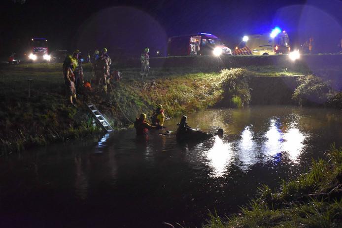 Hulpverleners zijn druk doende om de slachtoffers uit de auto te krijgen.