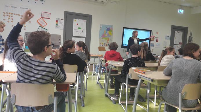 Leerlingen van groep 8 van De Stappen krijgen uitleg van Anouk van Gils hoe ze hun telefoontje boefproof kunnen maken.