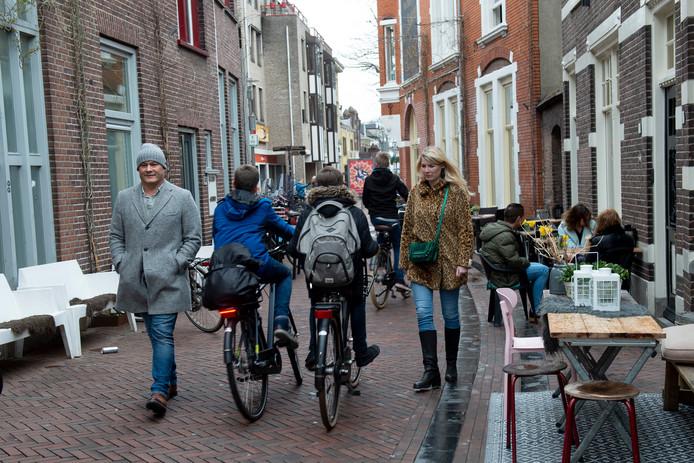 Fietsers tussen de voetgangers door en vlak langs de terrassen, dat gaat nog even door aan de Kapelstraat in Apeldoorn.