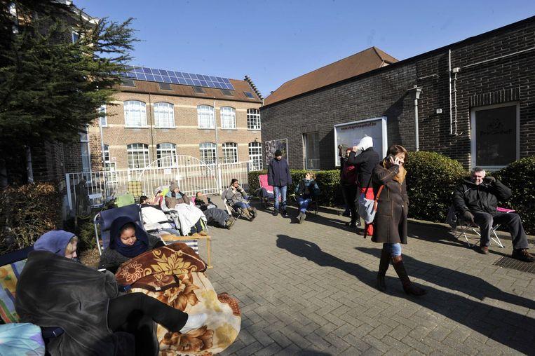 Grootouders en ouders wachten gezamenlijk aan de schoolpoort van school Prinsenhof om hun kleuters te kunnen inschrijven.