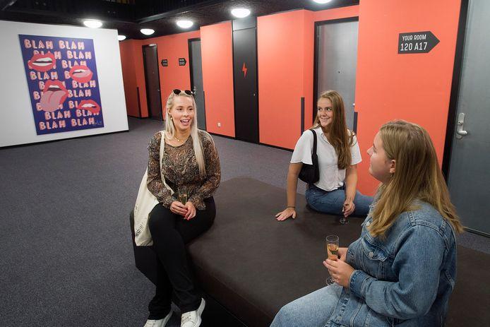 De drie eerstejaars studentes Anniek de Vries, Karenza de Koop en Elsa Moenen (van links naar rechts) in een zitruimte van hun studentencomplex in Breda.