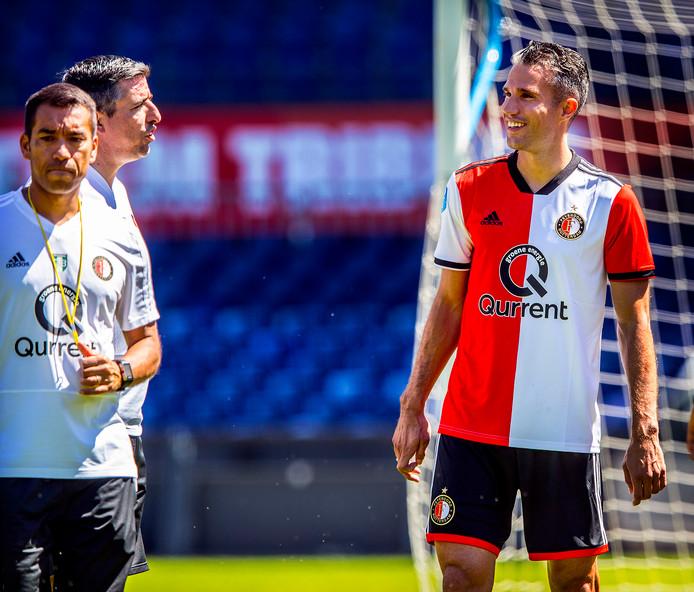 Robin van Persie lacht op de training, met links Giovanni van Bronckhorst.