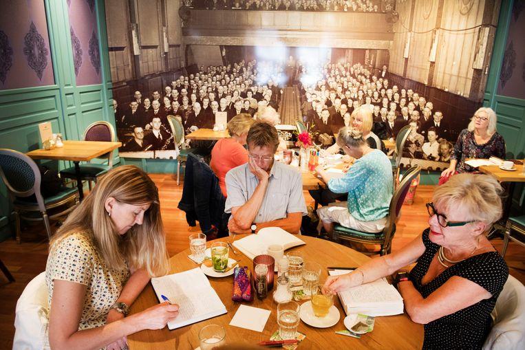 Deelnemers aan het schrijfcafé in het Alkmaarse café Het Gulden Vlies. 'Bij het voorlezen moet je even de schaamte voorbij. Maar een tekst krijgt meer muziek als je die deelt.' Beeld Olaf Kraak