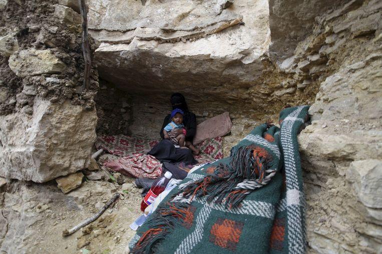 Een gevluchte vrouw met kind zit in een grot in het district Khamir, in de noordwestelijke provincie Amran. Beeld reuters