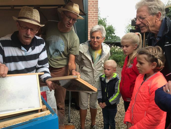 Irma en Hennie Broekman met hun kleinkinderen Fenne, Linne en Mats en de imkers Peter Aben (achter) en Ad van Houten (vooraan).