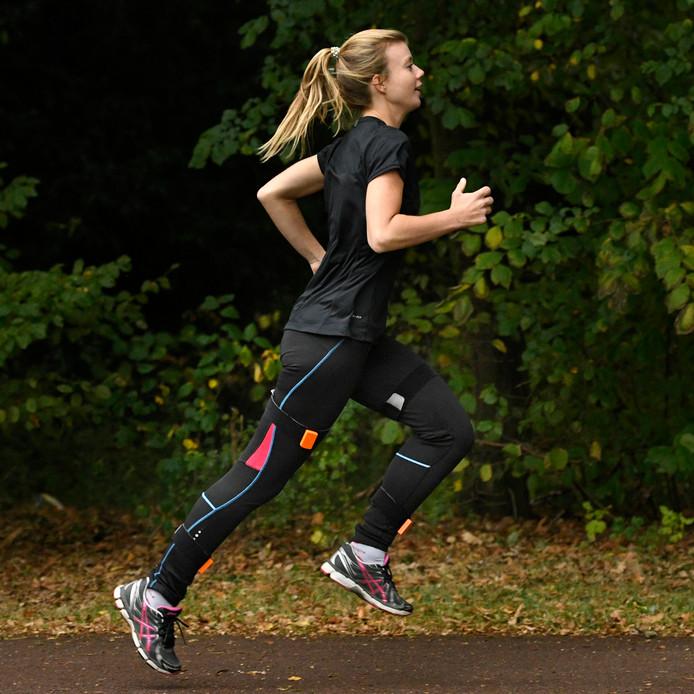 Hardloopster beplakt met sensoren. Via het sporthorloge of in de smartphone geplugde 'oortjes' geeft de Runner Assist advies.