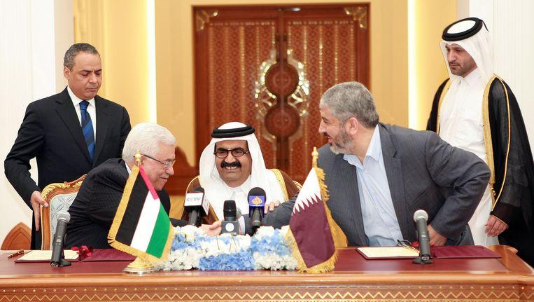 Khaled Mashaal, rechts, schudt de hand van Mahmoud Abbas, de Palestijnse president. In het midden de emir van Qatar. Beeld AP