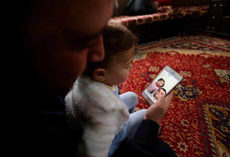 Vader en dochter bekijken het filmpje waarmee ze viraal gingen.